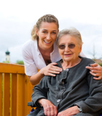 happy senior woman wearing glasses in wheelchair with a caregiver